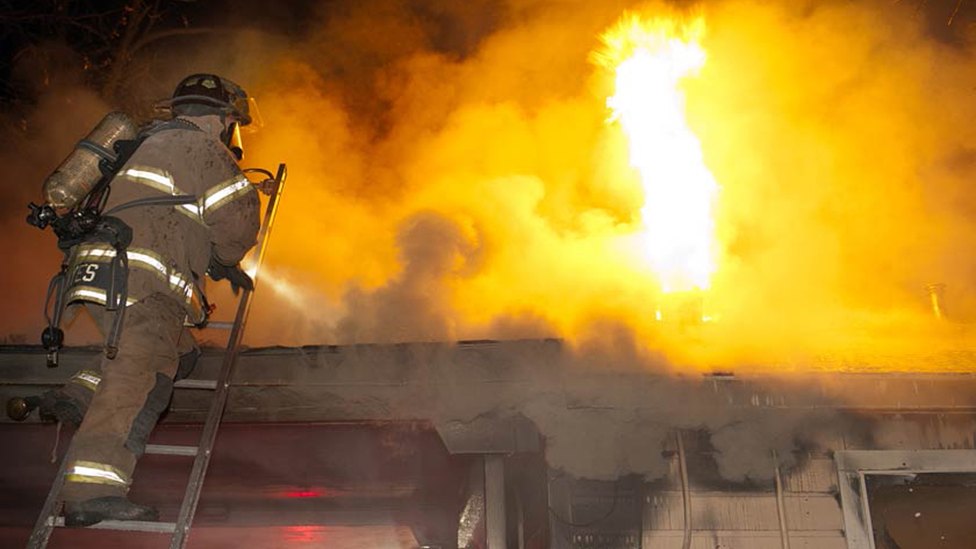 Fire Fighter on ladder with burning roof