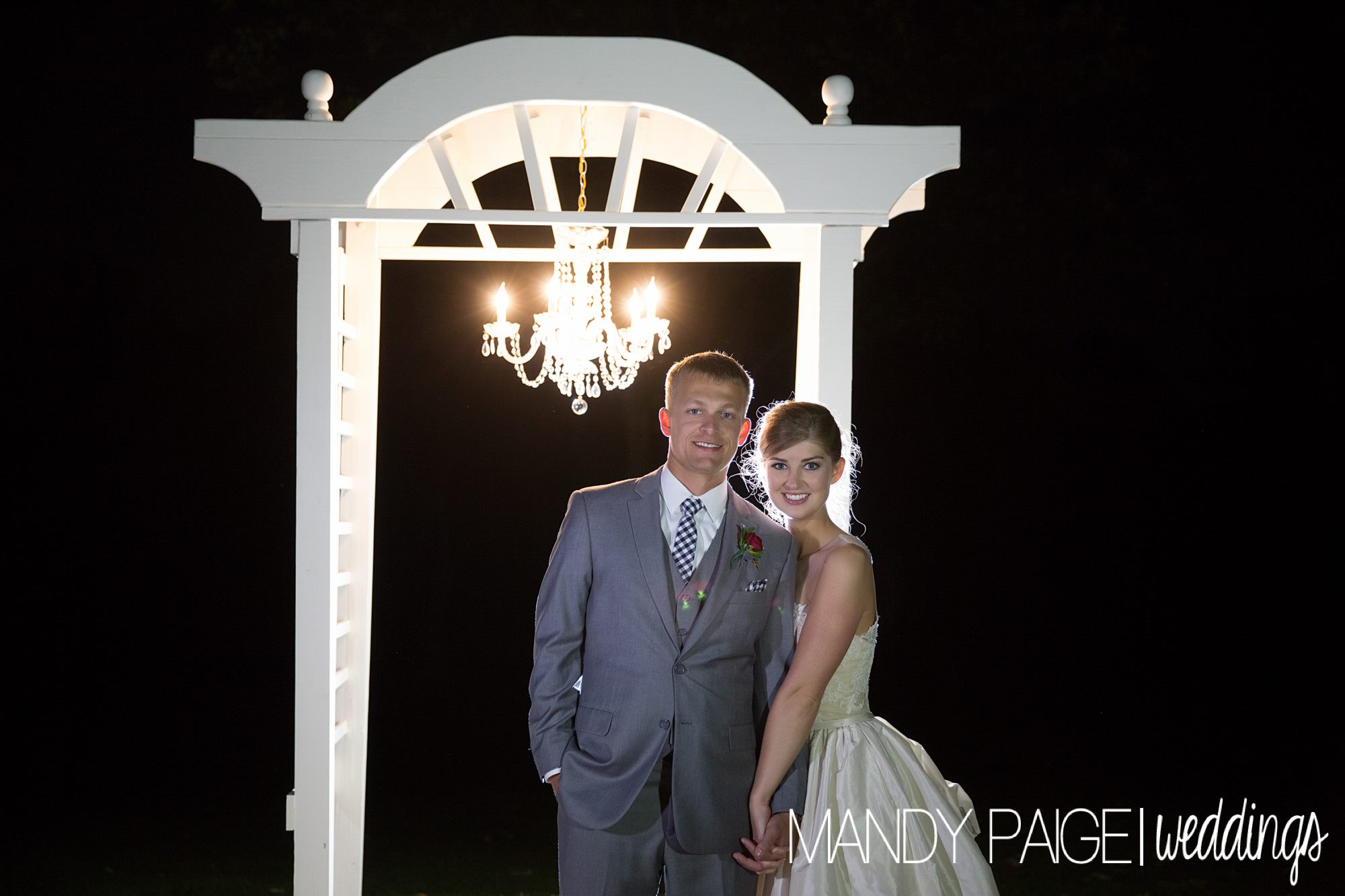 bride and groom at night with chandelier