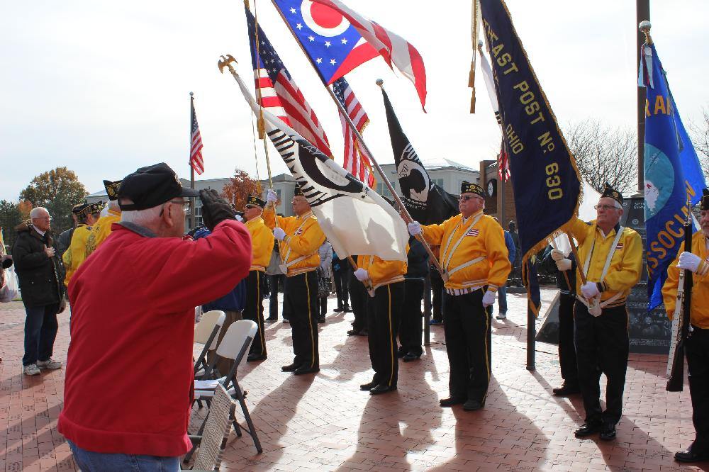 Man salutes Veterans Day ceremony participants with flags
