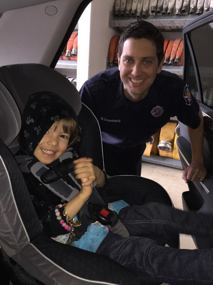 Firefighters with child in a car seat