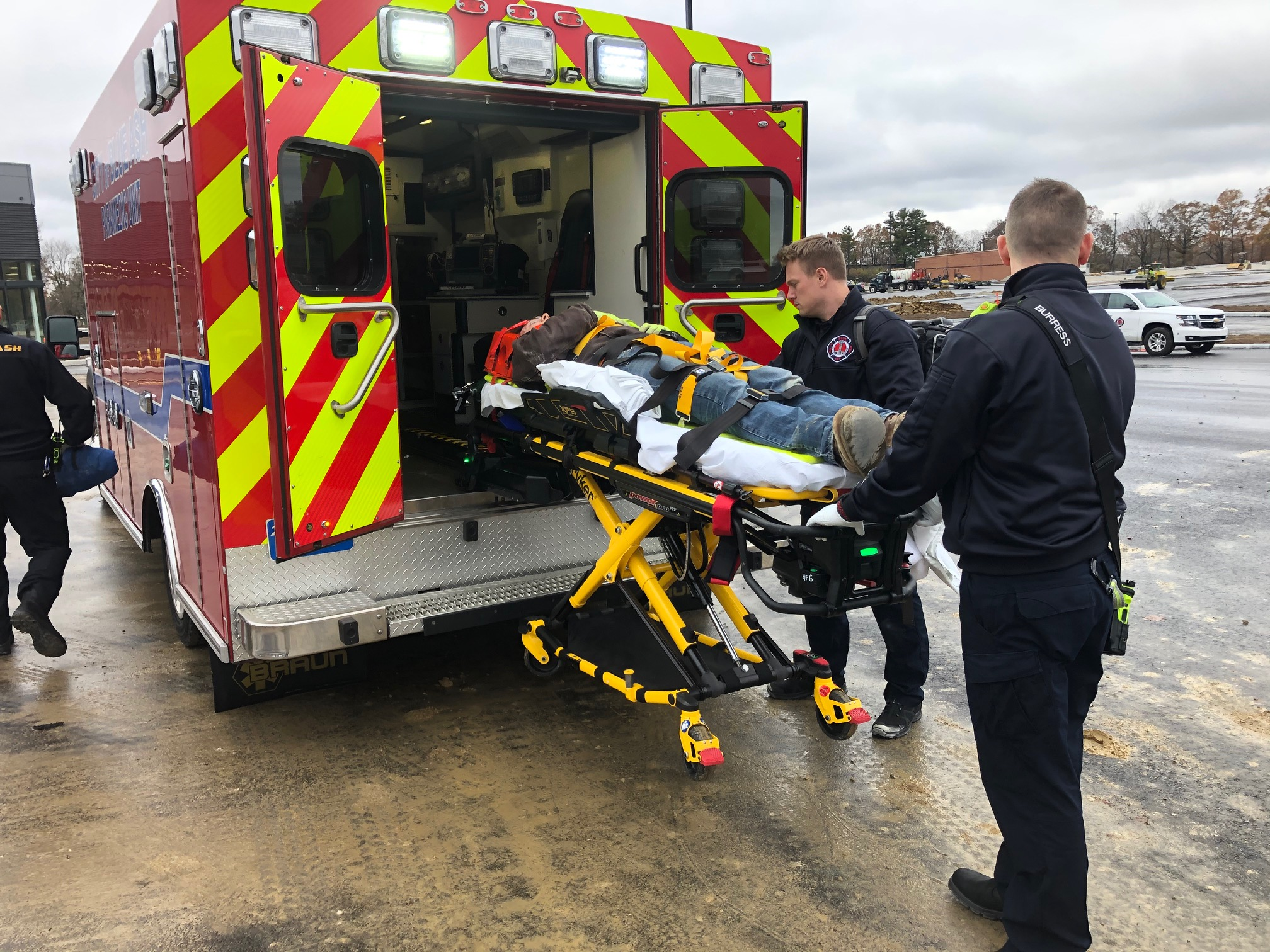 firefighters guide patient into ambulance during mock disaster drill