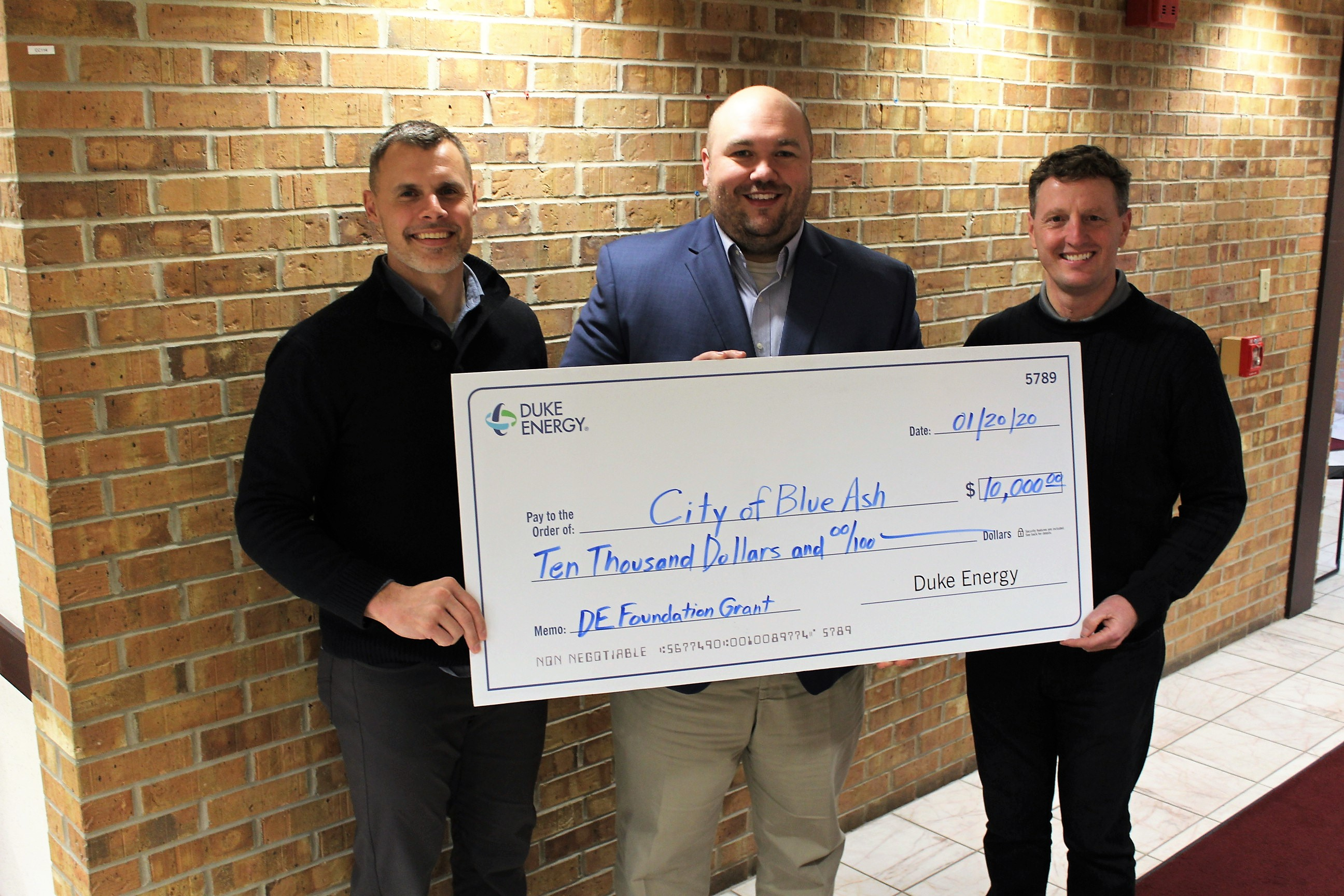 Blue Ash Parks and Recreation Director Brian Kruse, Duke Energy Sr. Government Affairs Specialist J. Chad Shaffer, and Blue Ash City Manager David Waltz holding giant check