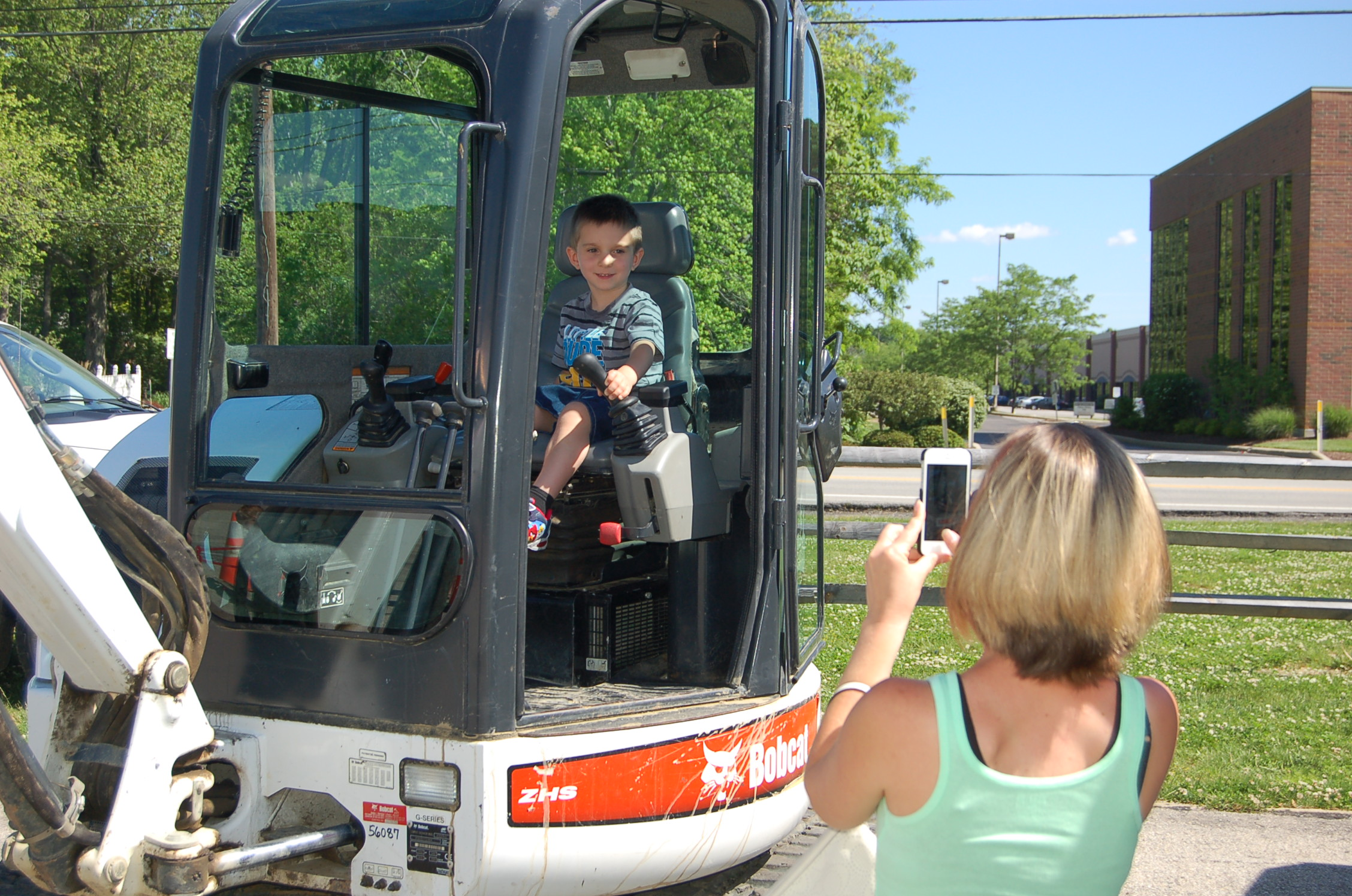 Mom taking photo of son in bobcat