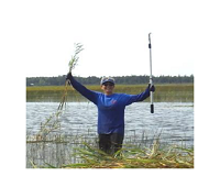 Woman victoriously holding up cut phragmites plant