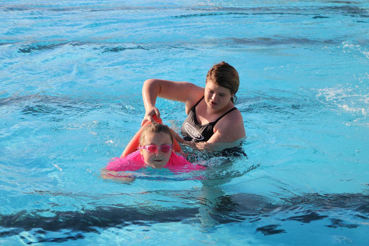 Life guard and girl working on kicking and arm movement - swim lessons